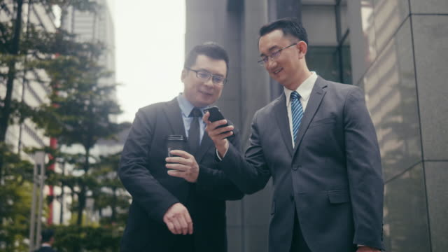 Two asian businessmen using smart phone on the street corner