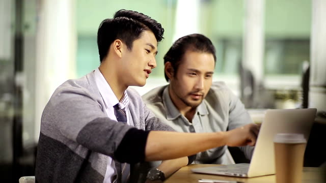 two asian businessmen working together in office video