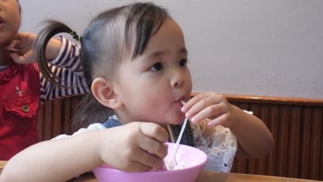 Two Asian children eat in a restaurant. video