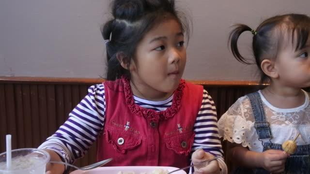 Duas crianças asiáticas comem em um restaurante. - vídeo