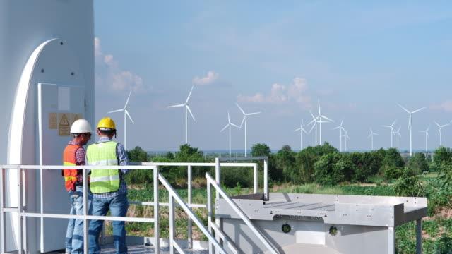 två asiatiska ingenjörer kontrollerar driften av vindkraftverk i vindkraft park fält för produktion av el kraft - vindsnurra jordbruksbyggnad bildbanksvideor och videomaterial från bakom kulisserna