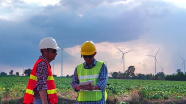 Two Asian engineers shake hands are checking the operation of wind turbines in wind farm field with digital tablet for production of electric power Two Asian engineers shake hands are checking the operation of wind turbines in wind farm field with digital tablet for production of electric power generation x stock videos & royalty-free footage