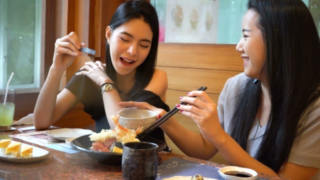 vídeos de stock e filmes b-roll de two asian female friends eating and having a meal together. women enjoying good time at japanese restaurant - tempura
