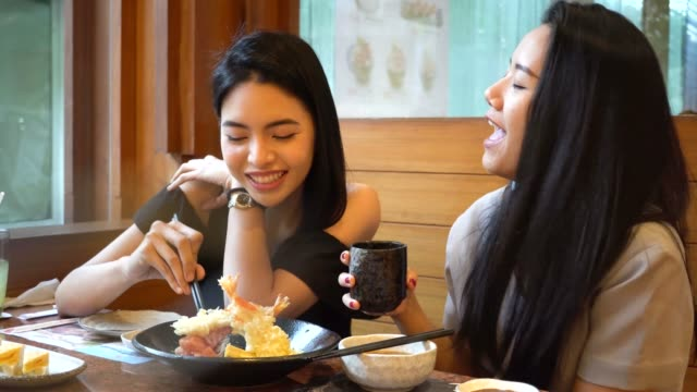 Two Asian female friends eating and having a meal together. Women enjoying good time at Japanese restaurant video