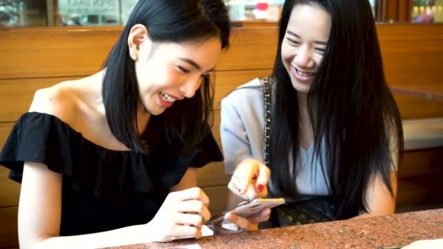 zwei asiatische freundinnen mit handy und gemeinsam lachen. frauen genießen gute zeit im japanischen restaurant - teenage friends sharing food stock-videos und b-roll-filmmaterial