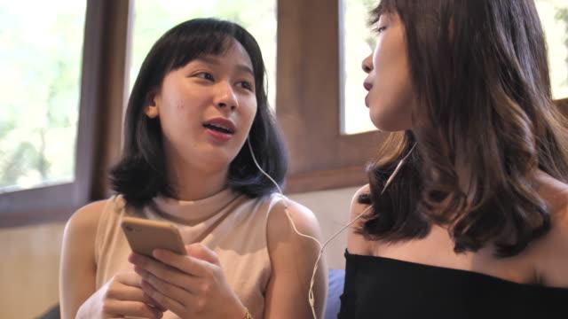 zwei asiatische freundinnen benutzen handy und lachen zusammen - teenage friends sharing food stock-videos und b-roll-filmmaterial