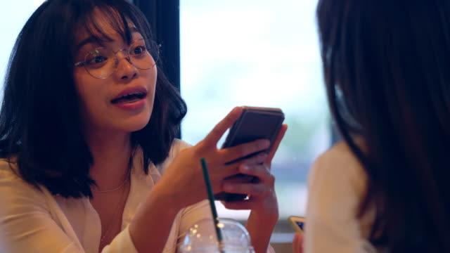 stockvideo's en b-roll-footage met twee aziatische vrouwelijke vrienden met behulp van mobiele telefoon in café - oost azië
