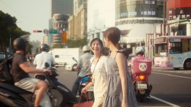 Two asian female influencers shopping and crossing street