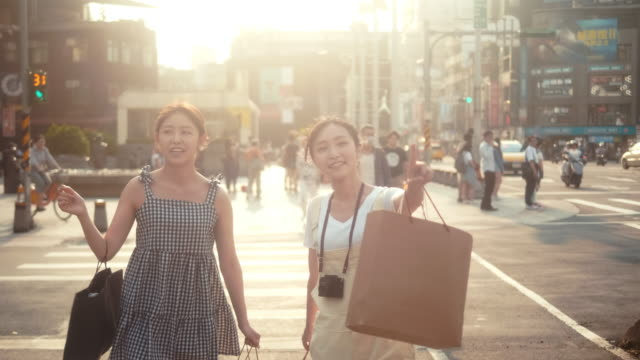 Two asian female influencers with shopping bags crossing street