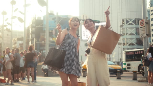Two asian female influencers with shopping bags pointing to the store (slow motion)
