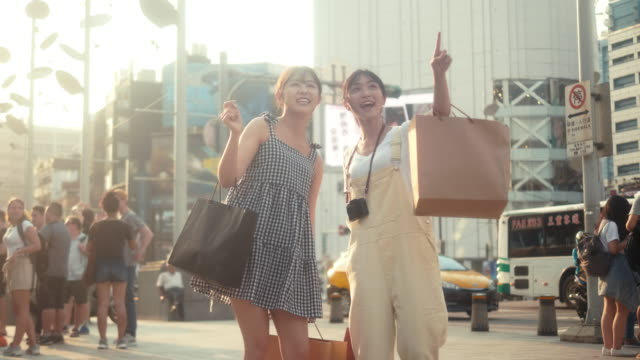 Two asian female influencers with shopping bags pointing to the store