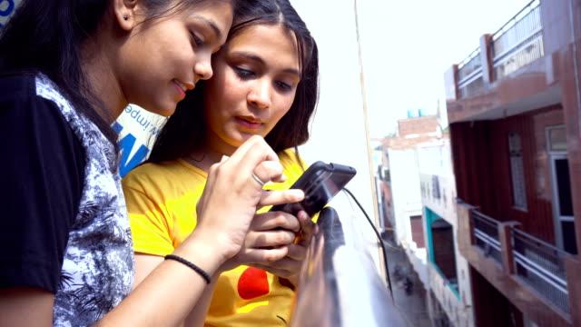 två asiatiska tjejer upptagen på smart phone - working from home bildbanksvideor och videomaterial från bakom kulisserna
