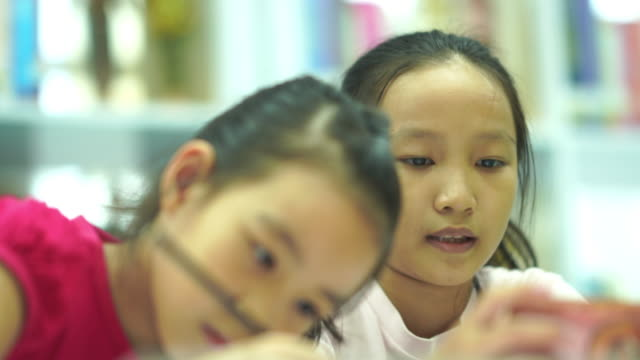 Two Asian girls e-learning together from smartphone
