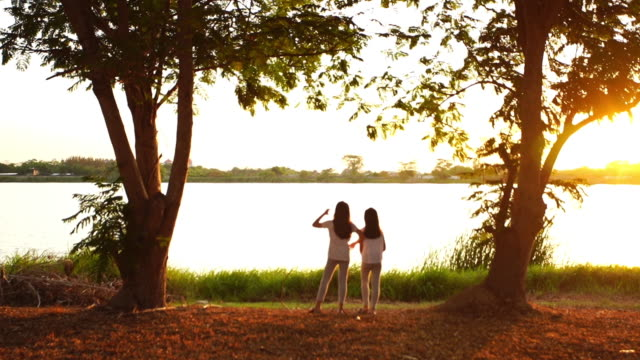 Two Asian girls playing at lakeside in evening - vídeo