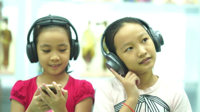 Two Asian girls singing and listening music from headphones