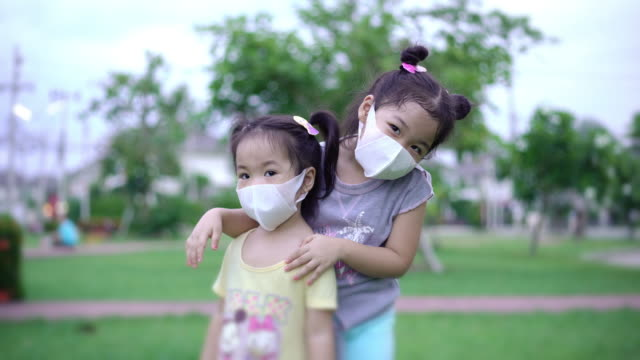 Two Asian girls smiling behind a protective face mask outdoors.