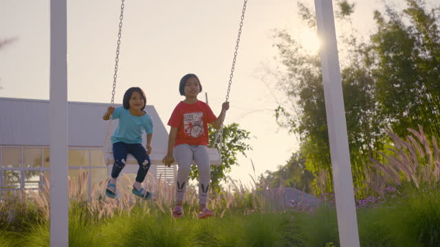 Two asian girls swinging happily in sunset time.
