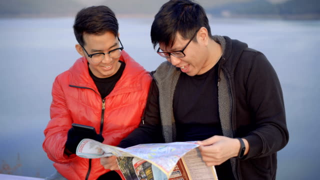 Two Asian Man looking at Map before walk away video