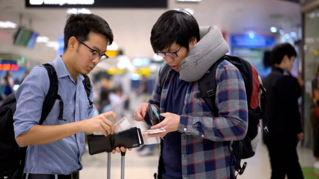 Two Asian men collect the money from for exchange rate service in airport