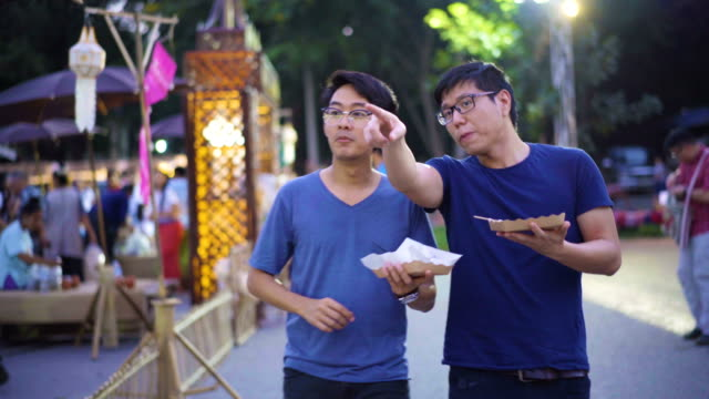two asian men eating and exchanging their food for thai traditional market - thai food stock videos and b-roll footage