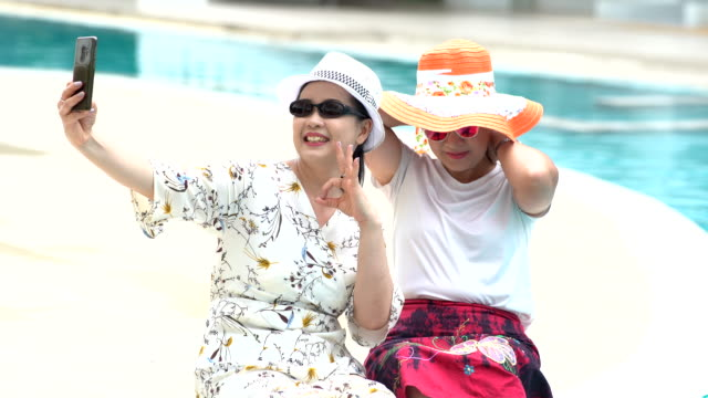 two asian older women relax time nest a swimming pool