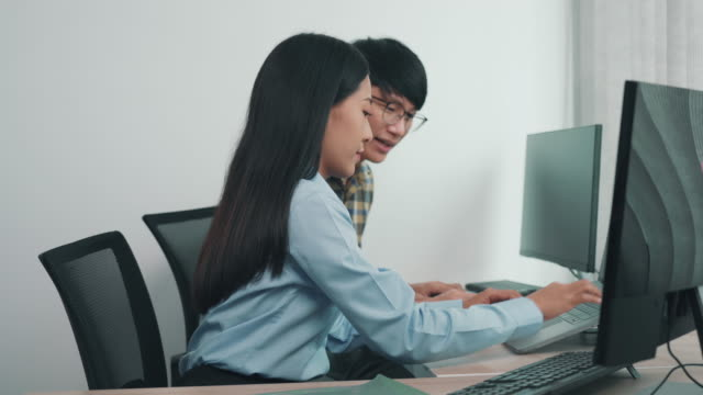 Two asian team working development of programming and encryption technology website design programmers on desk in office.