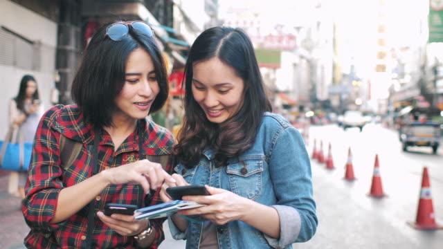 地図付きスマートポネを使用して2人のアジアの観光客 - 方向点の映像素材/bロール