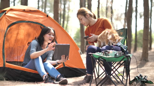 Two Asian Woman Friend Camping together and using Digital tablet