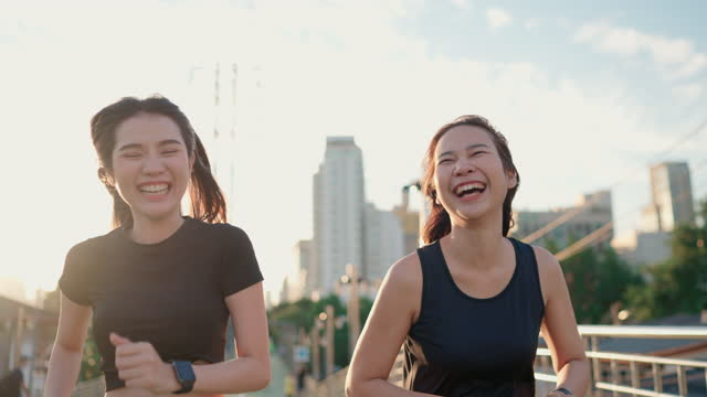 Two Asian woman jogging and checking her smart watch at public park