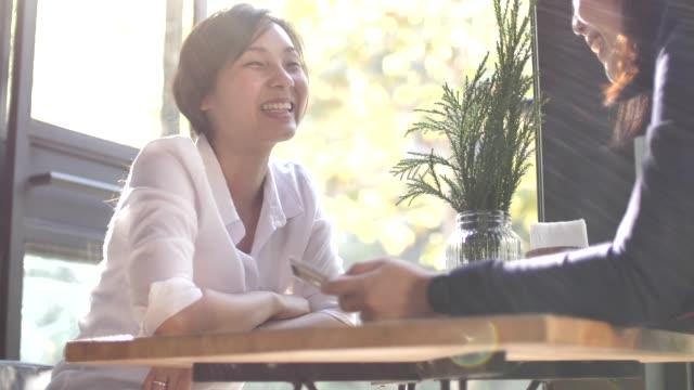 two asian woman sitting in the coffee shop and chatting - wygodny filmów i materiałów b-roll