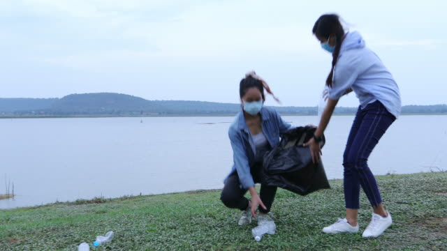 Two asian women picking up plastic bottles on the lake for environment Conservation video
