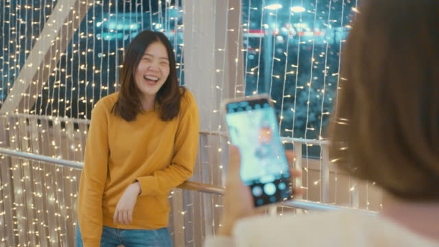 Two asian women taking photo with a mobile phone with lights decorated at Christmas