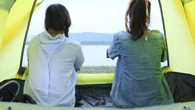 Two Asian women tourist drinking beer-alcohol together with happiness in Summer while having camping near lake