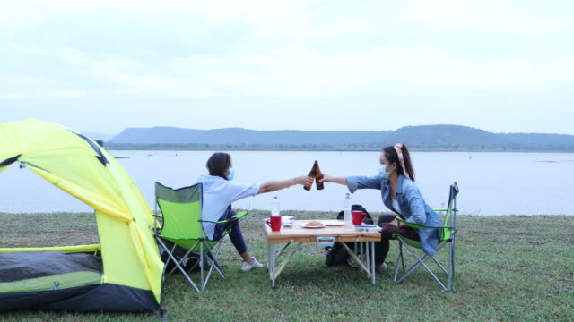 Two Asian women tourist drinking beer-alcohol together with happiness in Summer while having camping near lake video