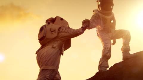 vidéos et rushes de deux astronautes escalade montagne colline entraider, atteindre le sommet. coup de main. surmonter les difficultés, moment important pour la race humaine. - courage