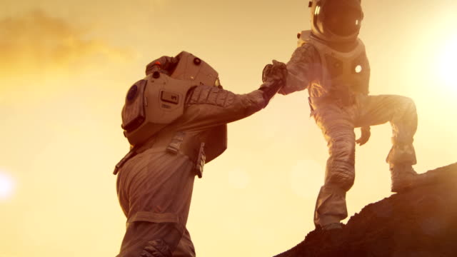 Two Astronauts Climbing Mountain Hill Helping Each Other, Reaching the Top. Helping Hand. Overcoming Difficulties, Important Moment for the Human Race. Two Astronauts Climbing Mountain Hill Helping Each Other, Reaching the Top. Helping Hand. Overcoming Difficulties, Important Moment for the Human Race. Shot on RED EPIC-W 8K Helium Cinema Camera. mountain peak stock videos & royalty-free footage
