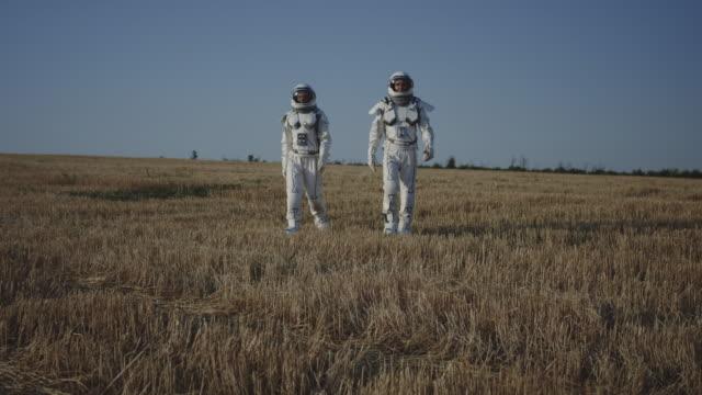 zwei astronauten überqueren ein feld - raumanzug stock-videos und b-roll-filmmaterial