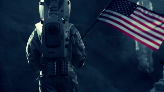 Two Astronauts Explore Alien Planet. One Carrying American Flag. Near Future and Technological Advance Brings Space Exploration, Travel, Colonization Concept. video