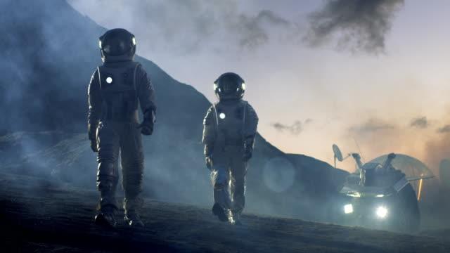 två astronauter i rymddräkter tryggt gå på främmande planet, utforskning av den planetens yta. i bakgrunden forskning base / station och rover. utrymme reser, colonization koncept. - mars bildbanksvideor och videomaterial från bakom kulisserna