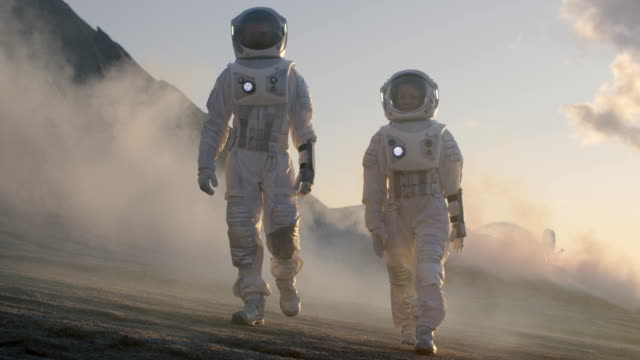 Two Astronauts in Space Suits Confidently Walking on Alien Planet, Exploration Expedition on the Planet's Surface that is Covered with Rocks, Gas and Smoke. Humans Overcoming Difficulties. Two Astronauts in Space Suits Confidently Walking on Alien Planet, Exploration Expedition on the Planet's Surface that is Covered with Rocks, Gas and Smoke. Humans Overcoming Difficulties.   Shot on RED EPIC-W 8K Helium Cinema Camera. group of animals stock videos & royalty-free footage