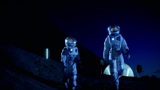 zwei astronauten in raumanzügen erkunden neu entdeckten planeten. in den hintergrund-raum-basis. futuristisches konzept auf raumkolonisation. - raumanzug stock-videos und b-roll-filmmaterial