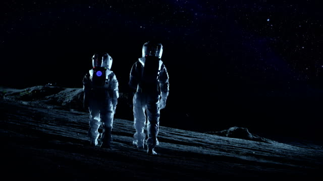 Two Astronauts in Space Suits Stand on the Alien Planets Looking at the Stars and Galaxies.  Space Travel and Extraterrestrial Colonization Concept. video