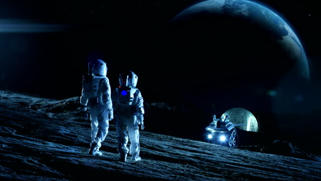 Two Astronauts in Space Suits Stand on the Moon Looking at the Beautiful Earth. In the Background Lunar Base with Geodesic Dome. Moon Colonization and Space Travel Concept. Establishing Shot. video