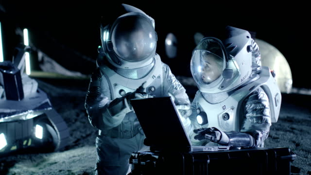 Two Astronauts Wearing Space Suits Work on a Laptop, Exploring Newly Discovered Planet, Send Communicating Signal to Earth. Space Travel, Interstellar Exploration and Colonization Concept. video