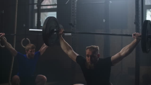 vídeos de stock e filmes b-roll de two athlete lifts the bar above himself, performing a jerk, a spinning push. 2 man with a beard is engaged in weightlifting on a dark background, portrait. concept strength, power, playing sports. - agachar se
