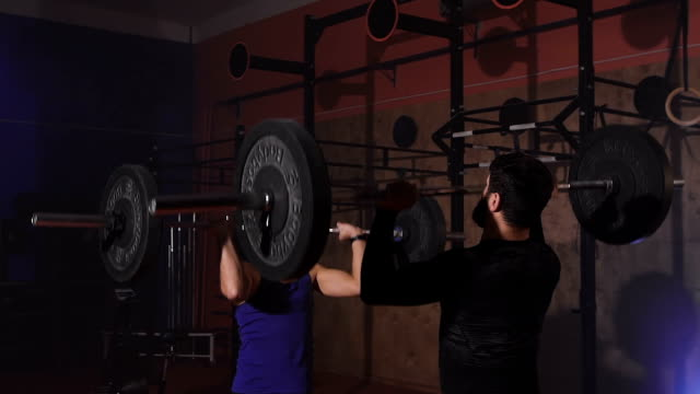 Two athletes at the same time lift the bar with weight video