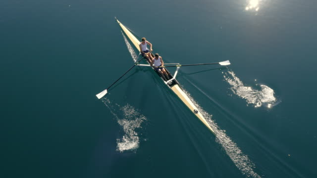 AERIAL Two athletes in a coxless pair gliding across a lake in sunshine video