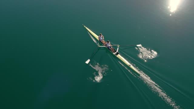 ANTENAS dos atletas de remo en un lago en un par sin timonel en un día soleado - vídeo
