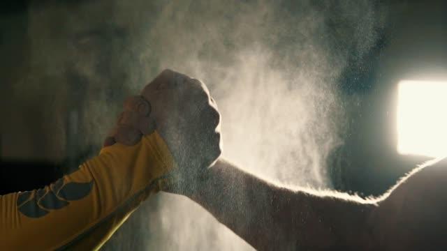 zwei athleten händeschütteln im fitness-studio, während ihre hände in magnesia behandelt werden - kreide weiss stock-videos und b-roll-filmmaterial