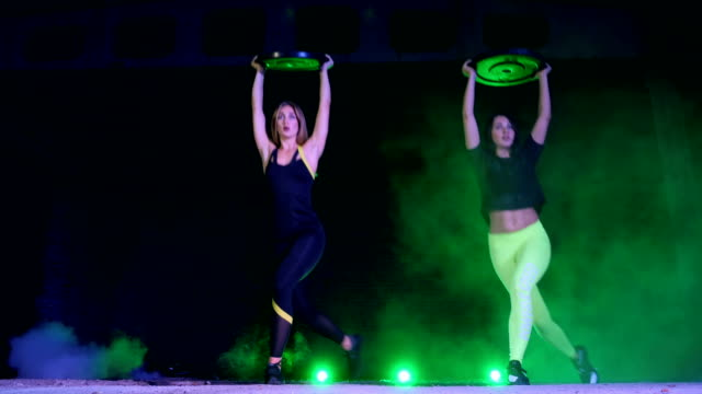 Two athletic, beautiful, women doing strength exercises with heavy weight plates, At night, in light smoke, fog, in light of multicolored searchlights, in an old abandoned hangar Two athletic, beautiful, women doing strength exercises with heavy weight plates, At night, in light smoke, fog, in light of multicolored searchlights, in an old abandoned hangar human back stock videos & royalty-free footage
